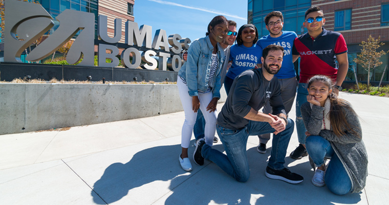 A diverse group of UMass Boston students in front of the sign outside the dorms